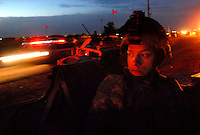 Sgt. Joseph Fernadez, 22 of Ely, Minn., watches from the gunner's hatch of his humvee as Iraqi police from the Emergency Services Unit (ESU) arrive in Bayji before dawn Tuesday. The Rakkasans provided support as the Iraqi ESU conducted a two day, 200 man sweep of the town.