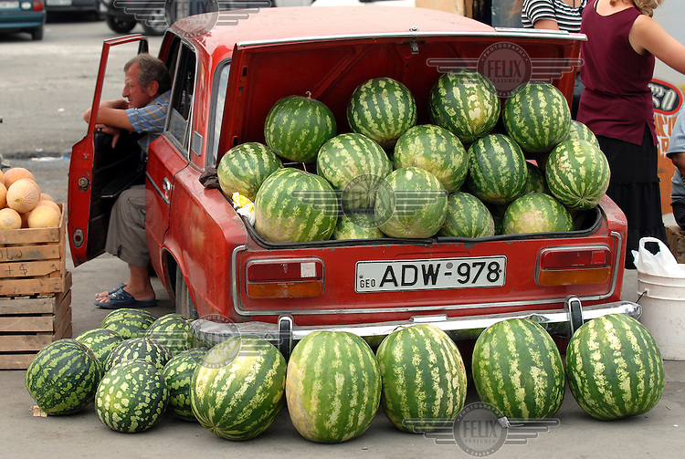 Man selling watermelons from the boot of his car at Didube bus and train station on the outskirts of Tbilisi.