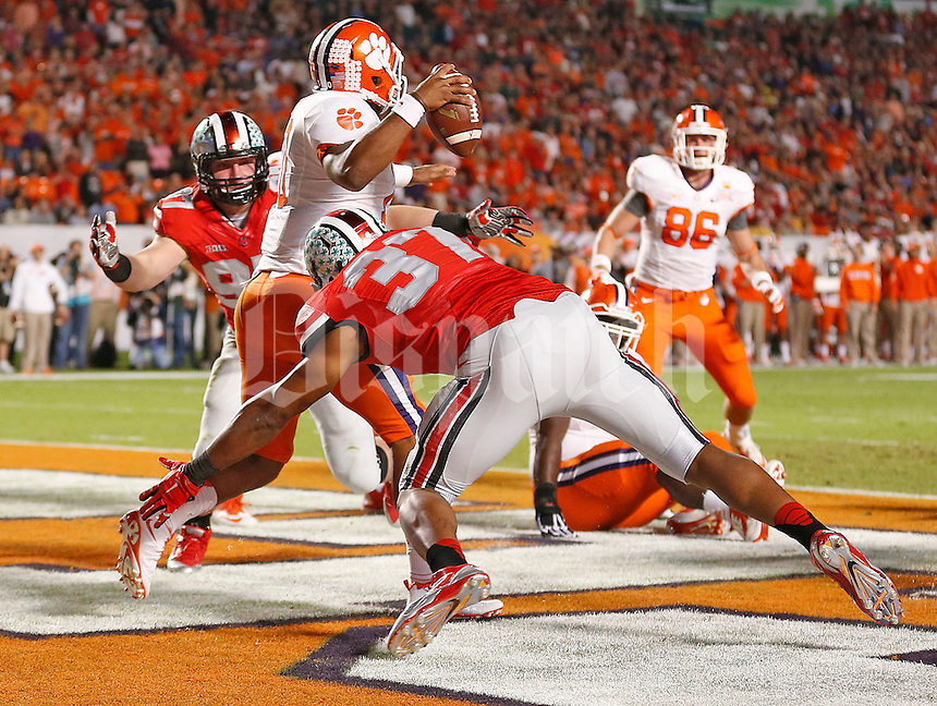 Ohio State Buckeyes defensive lineman Joey Bosa (97) and Ohio State Buckeyes linebacker Joshua Perry (37) combine to take down Clemson Tigers quarterback Tajh Boyd (10) for a safetyin the end zone in the 2014 Discover Orange Bowl at Sun Life Stadium in Miami Gardens, Florida on January 3, 2014. (Chris Russell/Dispatch Photo)