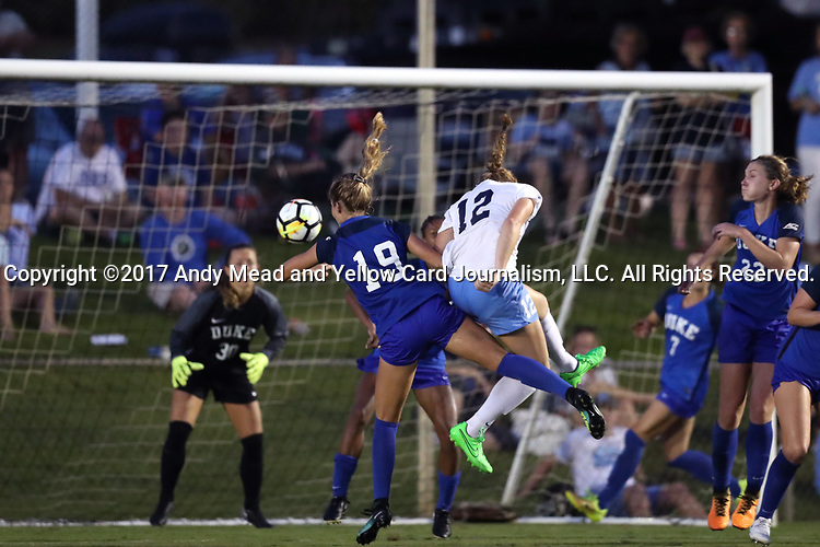 CARY, NC - AUGUST 18: North Carolina's Jessie Scarpa (12) beats Duke's Schuyler DeBree (19) to the ball and scores the sudden death game-winning goal in overtime. The University of North Carolina Tar Heels hosted the Duke University Blue Devils on August 18, 2017, at Koka Booth Stadium in Cary, NC in a Division I college soccer game.