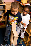 Preschool ages 3-5 boy and girl playing together in block area boy trying to blow over human figure on top of block vertical