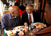 PHILADELPHIA - NOVEMBER 19: Yusuf Mohammed (L), and Eric Harrison (R), both of Philadelphia, have breakfast with Democratic Presidential Candidate General Wesley Clark (C) at the Harvest Vine November 19, 2003 in Philadelphia, Pennsylvania. Clark is stumping for votes over the next four days in Pennsylvania, New York, South Carolina, and North Dakota. (Photo by William Thomas Cain/Getty Images)