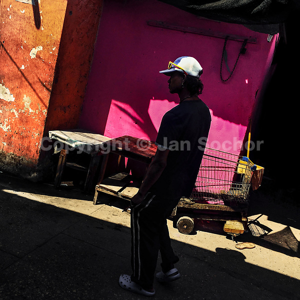 A Colombian man walks along a customized supermarket cart parked at the market of Bazurto in Cartagena, Colombia, 13 April 2018.