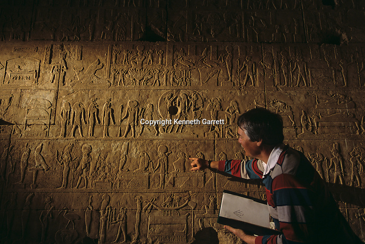 Eugene Cruz-Euribe examines reliefs found in Ptolemaic temple of Amun at Hibis the Darb el-Arbaein, trade route,Egypt; Archaeologist; Salima Ikram; Kharga Oasis;Ancient Cultures; mm7195; Desert; Oasis