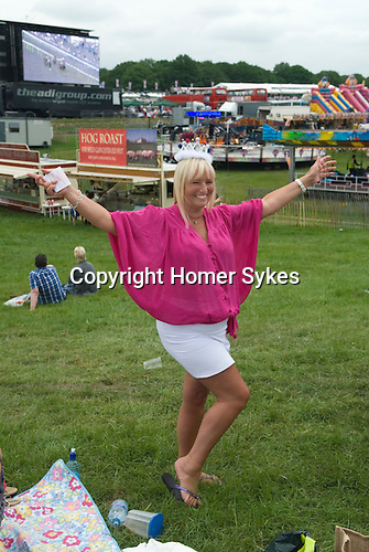 Ladies Day at The Derby horse race. Epsom Down Surrey UK. Deana Marshall wearing a royal crown to celebrate Queen Elizabeth's diamond jubilee. On the Hill, race track in background on large TV screen.