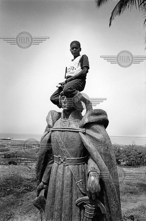 A boy sits upon the colonial statue of the 15th century Portuguese explorer and slave trader Nuno Tristao, which was dumped in the bush after the country's independence in 1974.