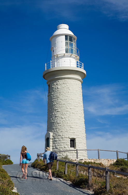 A couple walk up to Bathurst Lighthouse.  Rottnest Island, Western Australia, AUSTRALIA.
