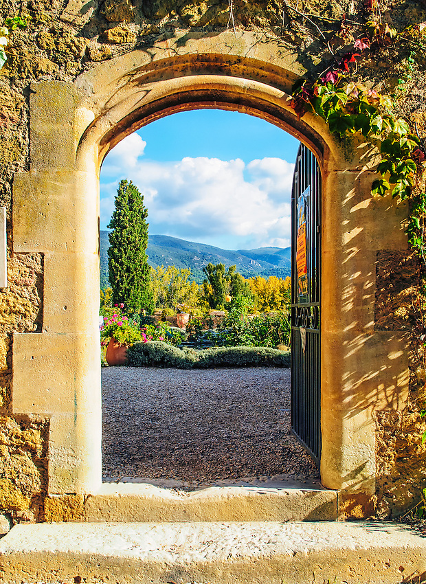View through an open doorway in the outer wall of the Château de Lourmarin, Lourmarin, France, showing the garden and the surrounding landscape.