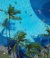 Tourists sunbathe and swim at the Hilton Hawaiian Village's luxurious pool.