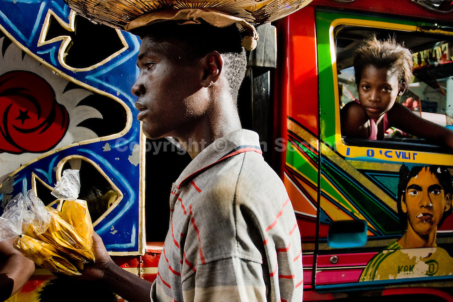 A Haitian street vendor sells banana chips to the tap-tap passengers on the street of Port-au-Prince, Haiti, 25 July 2008. Tap-tap vehicles serve as public transportation in Haiti. They are private, operate over fixed routes, departing only when full. Tap-taps are decorated with bright and shiny colors and with a lot of fancy designed elements. There are scenes from the Bible, Christian slogans, TV stars or famous football players often painted on a tap-tap body. Tap-tap name comes from sound of taps on the metal bus body signifying a passenger's request to be dropped off.