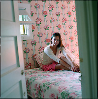 Woman sitting on bed in floral wallpapered bedroom