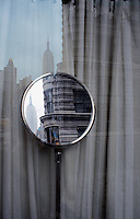 A reflection of the Empire State Building and the Flat Iron Building as seen from a storefront window.  New York 2002
