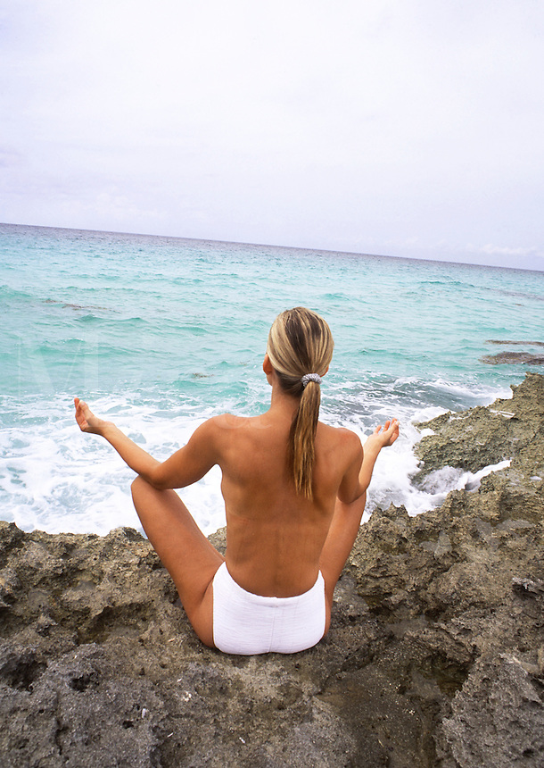 Woman meditating on rocky shore