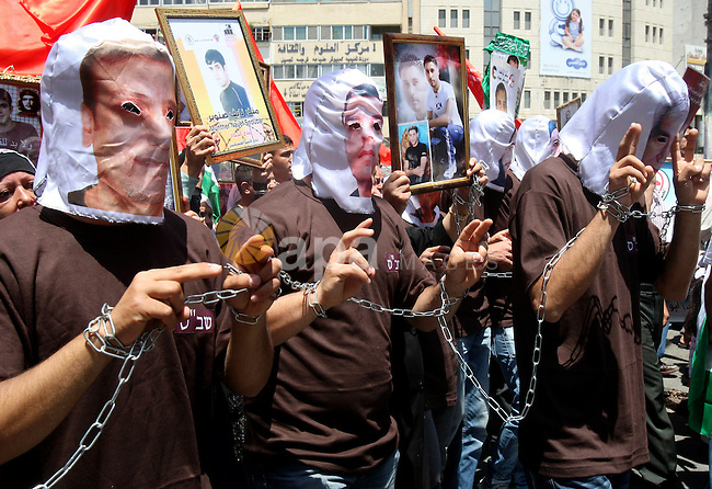 Palestinian protesters cover their faces with pictures of Palestinian prisoners during protests in the center of Nablus City , 12 May 2012 for the release of prisoners held in Israeli jails. Hundreds of Palestinians serving administrative detentions are currently on an open-ended hunger strike, with wide support in the Palestinian Authority and the Gaza Strip. Photo by Wagdi Eshtayah