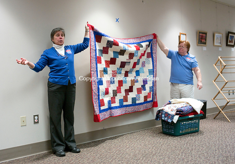 Cheshire, CT- 24 November 2015-112415CM05- Jane Dougherty, left, Co-coordinator with the Connecticut  Quilts of Valor Foundation and Carol Garrison, of Plymouth talk about a quilt at the Cheshire Library on Tuesday. Dougherty  gave a presentation about the Quilts of Valor Foundation which provides service members and veterans, touched by war with comforting quilts of valor both home and aboard.   Christopher Massa Republican-American