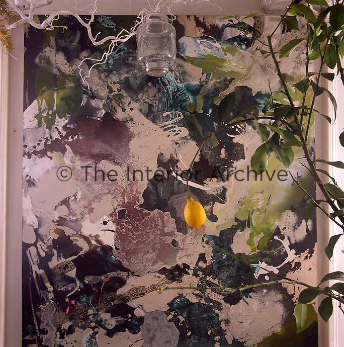 Inside florist Sue Daybell's garden room. A lemon tree with an abstract artwork behind.