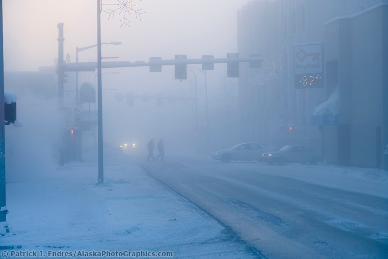 Pedestrians walk in the Ice fog in downtown Fairbanks, Alaska on a winter day with minus 40 degree temperatures.