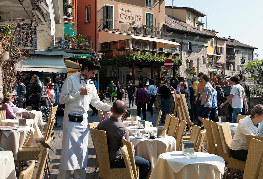 Italy, Lombardia, Sirmione, located on a small peninsula on the South Banks of Lake Garda: pavement cafes and restaurant at Old Town   Italien, Lombardei, Gardasee, Sirmione, auf einer Halbinsel am Suedufer des Gardasees gelegen: Cafes und Restaurants in der Altstadt
