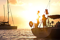 Man and woman on stern of yacht at sunrise in lagoon off Tahaa Island