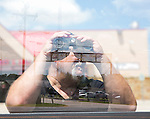 Eric Johnstone uses binoculars to view the main gate of Camp Swift from across the street at a gas station in Bastrop, Texas.