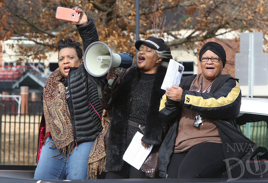 NWA Democrat-Gazette/DAVID GOTTSCHALK   Angela Mosley Monts, president of the Northwest Arkansas Martin Luther King, Jr. Council, Ocie Fisher and Katherine Williams lede the songs and chants as they participates Monday, January 16, 2017, in the annual Martin Luther King Jr. Freedom March to the campus of the University of Arkansas in Fayetteville. Participants in the march began near the corner of Razorback Road and Martin Luther King, Jr. Boulevard and marched, sang and chanted to the Arkansas Union for the Martin Luther King, Jr. Vigil co-sponsored by the University of Arkansas Associated Student Government, the Black Student Association and the Northwest Arkansas Martin Luther King, Jr. Council.