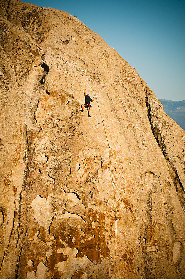"""Teenage boy rock climbing in the golden light of sunset at The City of Rocks, Idaho.  Route is named """"Scream Cheese""""  rated 5.9"""