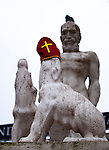 Dog statue wearing Saint Nicolas mitre during Sinterklaas parade, Dam Square, Amsterdam, 14th November 2010. The dog is a detail from the Dutch national monument, commemorating World War II. Sinterklaas, the basis for Santa Claus in other countries, arrives from Spain by boat,  accompanied by Black Peter, played by multitudes of white Dutch people in blackface - a tradition that evokes some controversy. Contrary to traditions of Santa Claus elsewhere, Sinterklass arrives by boat, then rides through the streets on his grey horse, Amerigo,  in mid-November, bringing in the Christmas season. The Zwarte Pieten (Black Peters) distribute sweets and gingerbread cookies to the crowd along the parade route.