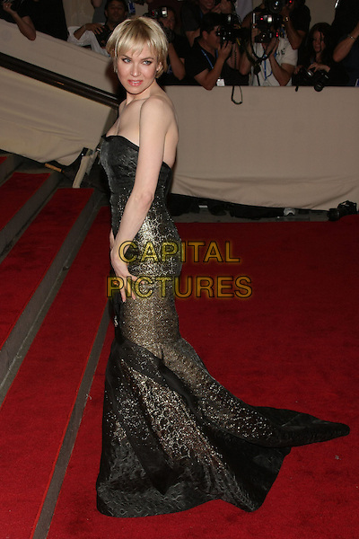 """RENEE ZELLWEGER.The Metropolitan Museum of Art's Costume Institute Gala """"American Woman: Fashioning A National Identity"""" held at the Metropolitan Museum of Art, New York, NY, USA..May 3rd, 2010.full length black maxi dress strapless gold fishtail bow sheer sparkly side .CAP/LNC/TOM.©TOM/LNC/Capital Pictures."""