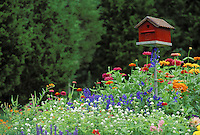 Red barn birdhouse with flowers