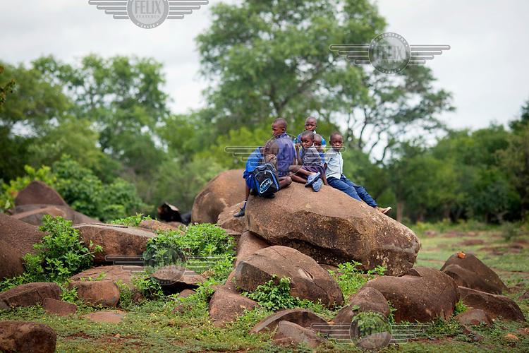 Pupils at Zvehuru primary school sitting on rocks near the school's borehole.