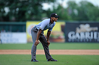 Umpire Edwin Moscoso works the bases in a game between the Greenville Drive and the Savannah Sand Gnats on Sunday, July 5, 2015, at Fluor Field at the West End in Greenville, South Carolina. Savannah won, 8-6. (Tom Priddy/Four Seam Images)
