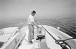 Captain Danny Mason aboard the OLD SALT maintains the net line that stretches into the distance.  Long-haul fishing involves towing a net between two boats for several hours.  The two boats drag the net to the shallows where the fish are captured.