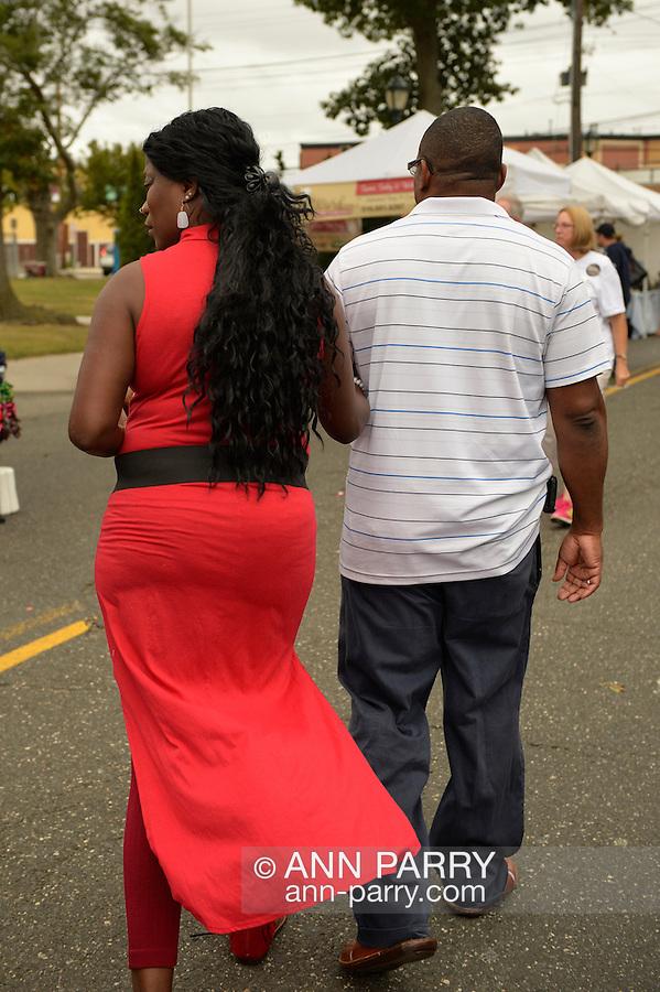 Merrick, New York, USA. 13th September 2014. A man and a woman wearing a long red dress visit the 23rd Annual Merrick Fall Festival & Street Fair in suburban Long Island.
