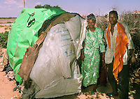 Siidow and his wife Moxodo stand by their home on the International Red Cross Compound in Mogadishu, Somalia in Feb. 1993. The hut is made from sticks, tarps and a bag which once contained rice collected by school children in France and shipped to Somalia.
