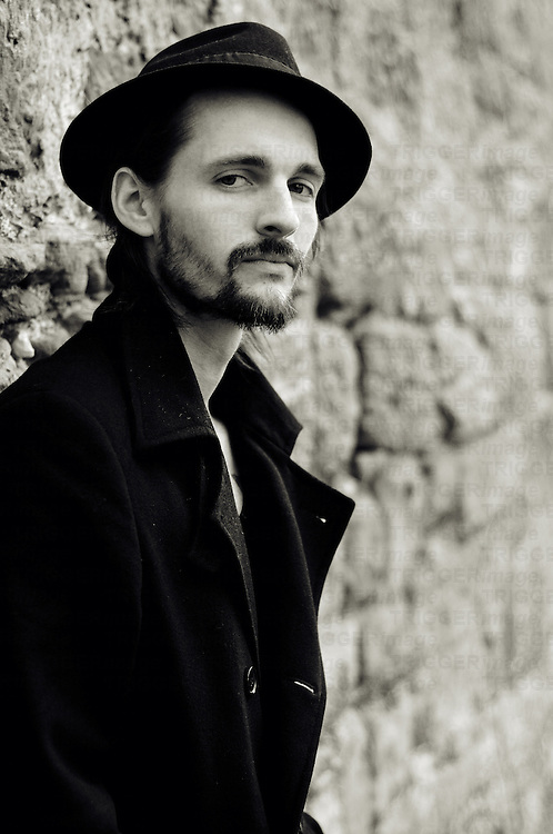 young bearded man in a coat and with a hat on is leaning against a wall of old sandstone.