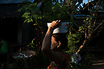 A woman walks through Shwethaungyan Township as the sun sets.