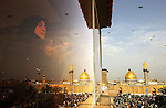 KARBALA, IRAQ–MARCH 18: An Iraqi woman prays on March 18, 2006 as Imam Abbas mosque  is seen  in the holy Shiite city of Karbala south of Baghdad, Iraq. Tens of thousands of Shiite Muslims are expected to arrive in the holy Shiite city of Karbala to mark Arbaniya, the 40th day after the death anniversary of Imam Hussein, grandson of Prophet Muhammad. (Photo by Wathiq Khuzaie /Getty Images).......