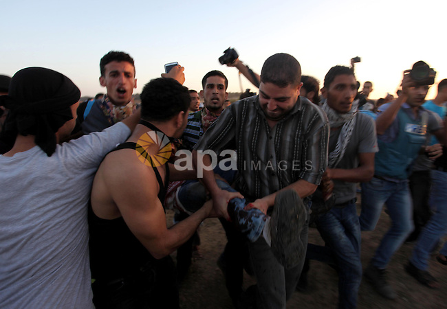 A Palestinian protester is evacuated by comrades after being injured during clashes with Israeli troops near a border fence between Israel and the Gaza Strip on October 14, 2015 east of Bureij in central Gaza. The outbreak of violence between Palestinians and Israeli forces in recent weeks has worsened in October, raising fears of a third intifada, or uprising. Photo by Ashraf Amra