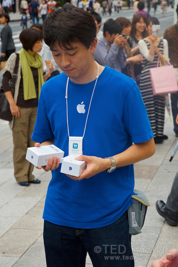 Apple Store employee ponders iPhone 4s while managing queue outside Ginza Apple Store in Tokyo, Japan. October 15, 2011