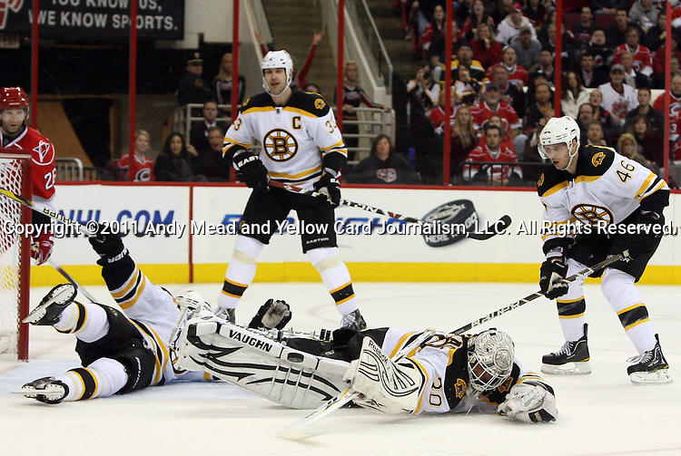 01 February 2011: Boston's Tim Thomas (30) makes a save as teammate Andrew Ference (left) dives across the crease and Zdeno Chara (33) and David Krejci (46) watch the play. The Carolina Hurricanes lost 3-2 to the Boston Bruins at the RBC Center in Raleigh, North Carolina in a 2010-2011 regular season National Hockey League game.