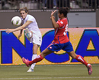 Kelley O'Hara, left, of the United States crosses the ball in front of Daniela Cruz of Costa Rica during play in the CONCACAF Olympic Qualifying semifinal match at BC Place in Vancouver, B.C., Canada Friday Jan. 27, 2012. The United States won the match 3-0 to earn a berth in 2012 London Olympics.
