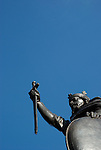 Upper portion of King Alfred statue against large area of plain blue sky, Winchester, England