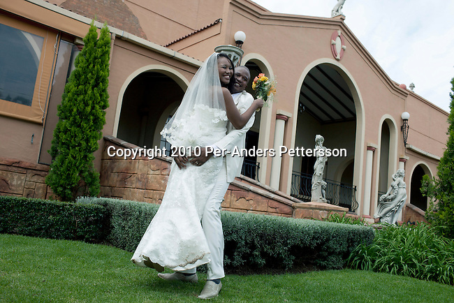 JOHANNESBURG, SOUTH AFRICA - MAY 1: Siphokazi Cola, age 26, and Xolile Ngambane, age 28, dance as they celebrate their wedding day at the Tuscan Wedding village on May 1, 2010, in Johannesburg, South Africa. They pose for the wedding photographer with relatives and friends outside the Tuscan style reception hall. Newly rich black entrepreneurs, such as this couple, love to throw lavish Western styled white weddings for hundreds of people. This Tuscan wedding theme village venue has a waiting list for two years. The couple went through a traditional and colorful wedding the following day at home. (Photo by Per-Anders Pettersson)