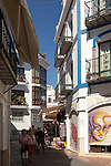 People exploring narrow streets at popular holiday resort town of Nerja, Malaga province, Spain