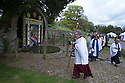 14/05/15<br /> <br /> The clergy members arrive to bless Hall Well - the village's main well situated opposite Tissington Hall. This year showing a Biblical design based on Elijah and the Ravens.<br /> <br /> To mark ascension day this year's well dressings are unveiled and blessed by the local clergy in the Derbyshire village of Tissington in the Peak District National Park.<br /> <br /> Before today's blessings, wooden boards coated in clay are decorated with tens of thousands of petals, leaves and pieces of foliage to create the giant intricate mosaics. The boards,  take teams of many villagers three days to make. <br /> <br /> The village has been decorating its six wells every year for more than six hundred years. The tradition is believed to be a celebration of the wells never running dry, giving life and  sustaining the village during times of plague. After a church service today (Thursday)  clergy from six parish will bless each of the well.  <br /> <br /> Following in Tissington's footsteps many other villages in the Derbyshire area also have their own well dressing traditions.<br /> <br /> <br /> All Rights Reserved: F Stop Press Ltd. +44(0)1335 418629   www.fstoppress.com.
