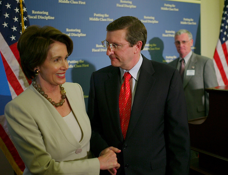 05/17/07--House Speaker Nancy Pelosi, D-Calif., and Senate Budget Chairman Kent Conrad, D-N.D., congratulate each other at the close of a news conference after the Democratic-led Congress adopted a $2.9 trillion fiscal 2008 budget resolution Thursday that sets up a showdown with President Bush over domestic spending. In background is Col. Steve Strobridge (USAF Ret.), of the Military Officers Association of America. Final action came when the Senate adopted the measure by a 52-40 vote, shortly after the House had approved it. The budget resolution (S Con Res 21 Ñ H Rept 110-153), adopted by 214-209 vote in the House, sets an overall discretionary spending cap for fiscal 2008 of $954.1 billion, not including war spending. The total is $21 billion more than the White House request for non-war spending, a figure that grows to $23 billion if $2 billion in advance appropriations are counted. The White House has threatened to veto domestic spending bills that exceed BushÕs budget, and House Republican conservatives are now collecting signatures on a letter promising to sustain those vetoes. Republican Study Committee Chairman Jeb Hensarling, R-Texas, said Thursday that he already has at least 60 signatures on a letter that will be released if and when it gets enough signatures to show that more than one-third of the House would vote to sustain vetoes. (A two-thirds majority vote in each chamber is needed to override a presidential veto.) Despite a deficit projection of $252 billion in the coming fiscal year, Democrats hailed their budget for boosting domestic spending while projecting a surplus of $41 billion in 2012. Congressional Quarterly by Photo Scott J. Ferrell