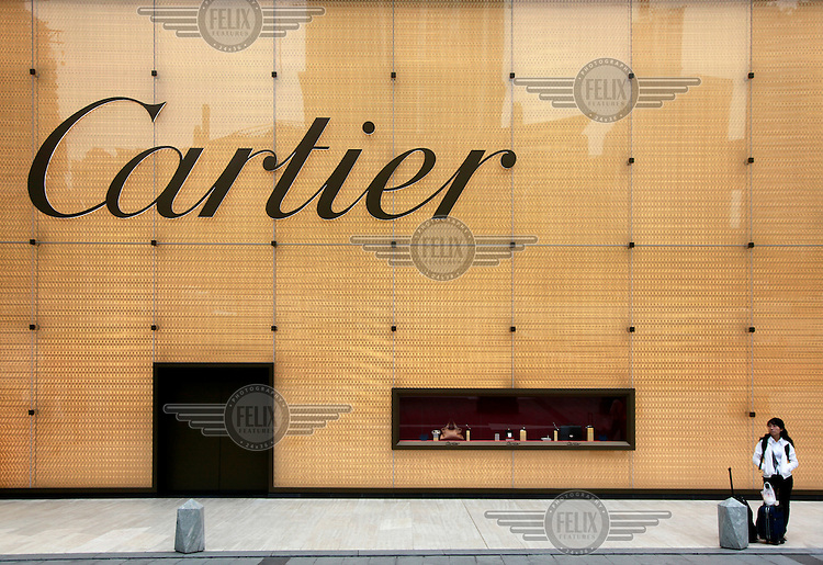 A woman stands outside a Cartier store at a luxury shopping centre.