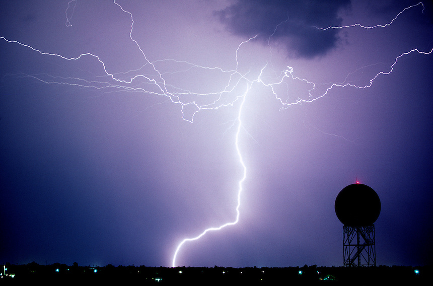 A combination of cloud-to-cloud and cloud-to-ground lightning heralds the approach of severe thunderstorms over a research Doppler weather radar at the National Severe Storms Laboratory in Norman Oklahoma.