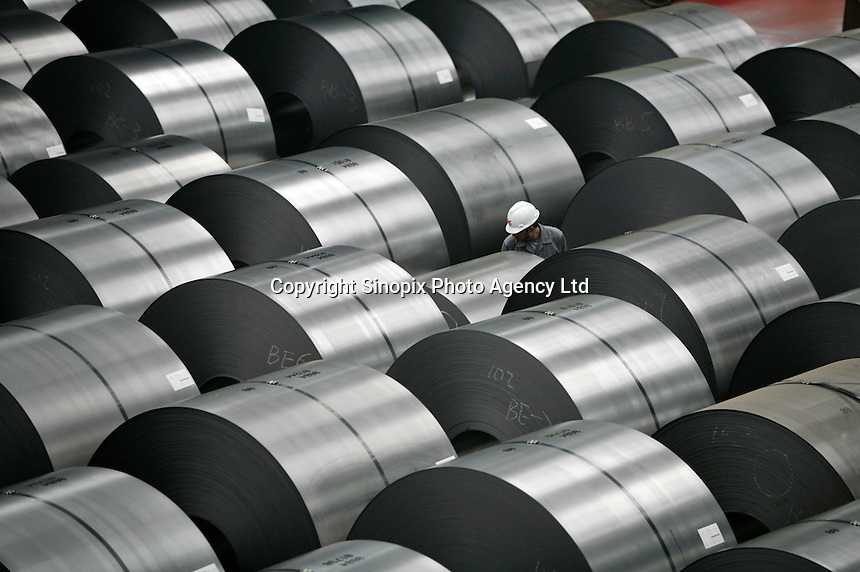 A worker inspects and marks rolls of steel plates at Ma Steel (Maanshan Iron & Steel Co.) in Maanshan, Anhui Province, China. ©Qilai Shen/Sinopix