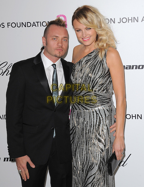 MALIN AKERMAN & GUEST .at the 19th Annual Elton John AIDS Foundation Academy Awards Viewing Party held at The Pacific Design Center Outdoor Plaza in West Hollywood, California, USA, February 27th 2011..oscars half length one shoulder dress silver grey gray patterned clutch bag suit tie sequined sequin sparkly                                                                                .CAP/RKE/DVS.©DVS/RockinExposures/Capital Pictures.